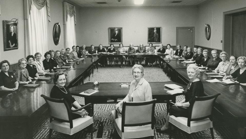 Belle S. Spafford, Marianne C. Sharp y Louise W. Madsen con la junta general de la Sociedad de Socorro, 1962. Con miembros de la presidencia al frente de la mesa (de izquierda a derecha: Madsen, Spafford y Sharp) Consejo general de la sociedad de Socorro en el edificio de la Sociedad de Socorro. Las miembros de la Junta formaron unidades de la Sociedad de Socorro en todo el mundo, supervisaron la producción de prendas de vestir de los templos, publicaron la Revista de la Sociedad de Socorro y crearon el plan de estudios de la Sociedad de Socorro.