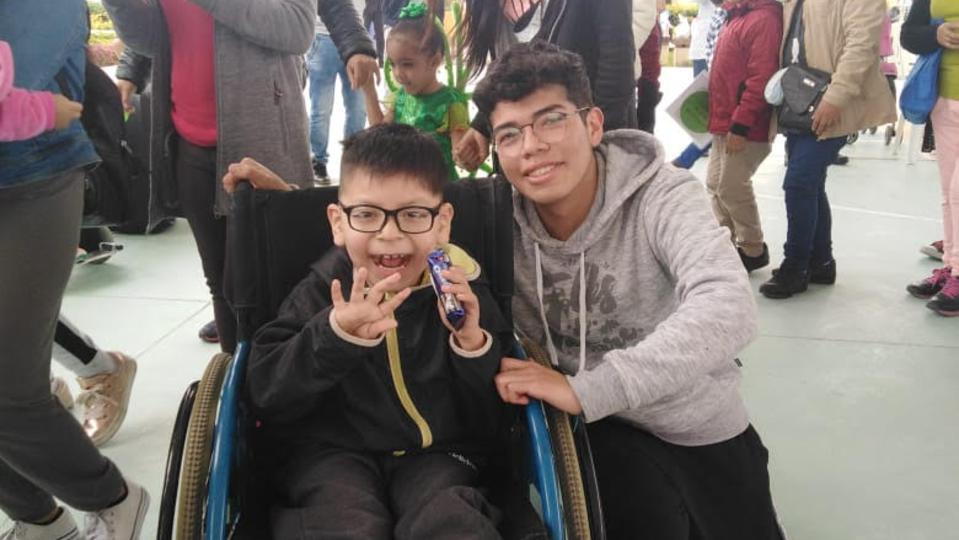 Hombres y Mujeres Jóvenes llevan alegría a los niños con parálisis cerebral