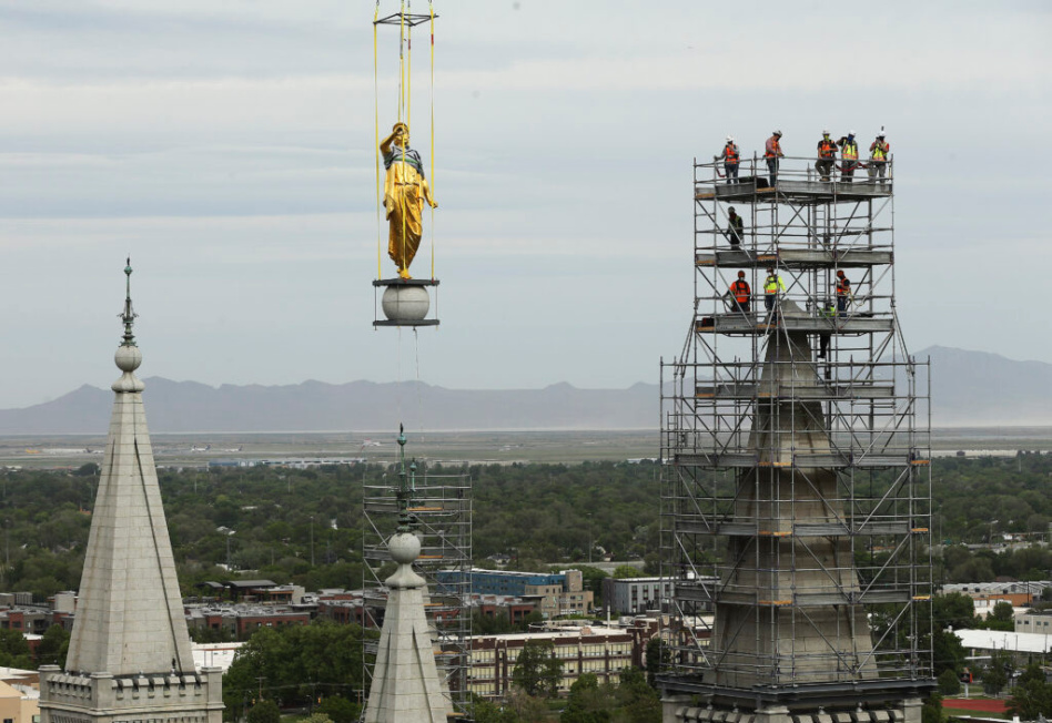 La estatua del ángel Moroni es trasladada por una grúa para su remodelación.
